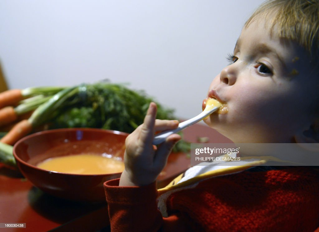 A child eats a vegetables soup on January 24, 2013 in Lyon, Central France. Organic Risotto, frozen ratatouille, stew the fresh : babies are courted by brands touting a new generation of small pots, competing on the bio market.