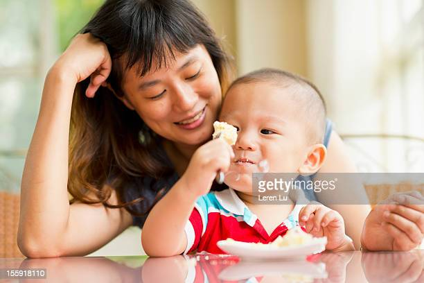 Child eats cheese cake with mother.
