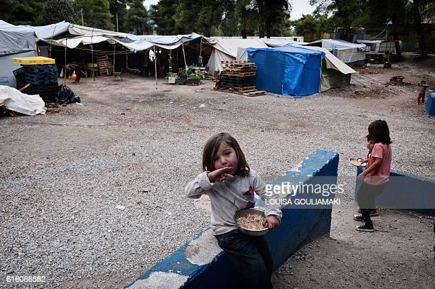A child eats her meal cooked by a volunteers' refugee team with a Syrian refugee chef at the Ritsona refugee camp north of Athens on October 21 2016...