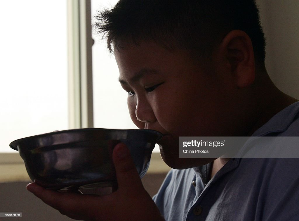 A child eats lunch at a base of the Aimin Slimming Centre on July 11, 2007 in Wuhan, Hubei Province, China. Doctors in the center have combined acupuncture, exercise and diet to help about 110 obese teenagers from 9 to 20 years old lose weight during one month. An official from the Ministry of Health revealed that more than 200 million Chinese people are overweight.