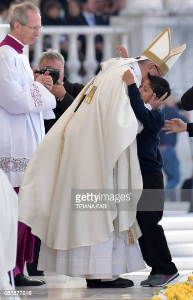 A child embraces Pope Francis during the celebration of a centenary mass marking the apparition of the Virgin Mary at Fatima's Sanctuary central...