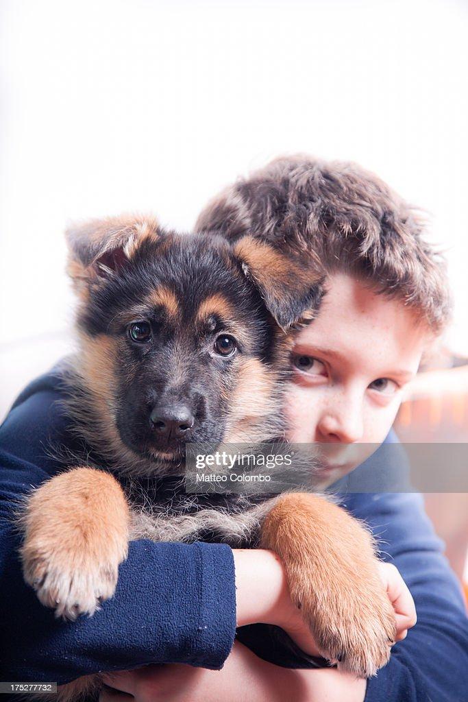 Child embracing german shepherd puppy dog : Stock Photo