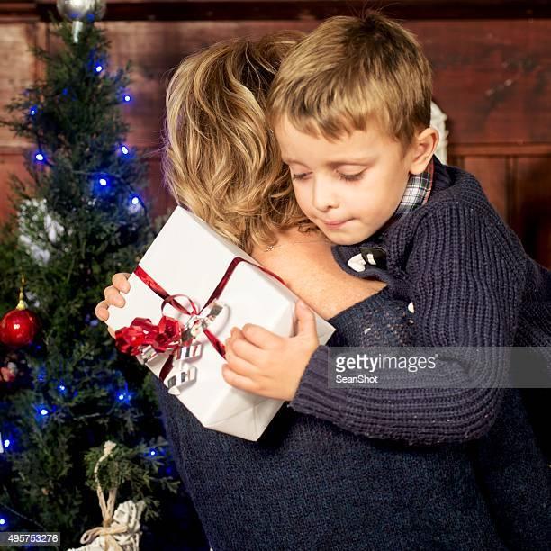 Kind umarmt Mutter mit einem Geschenk in der Hand