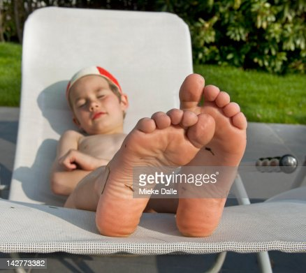 Child enjoying the sun on a lounger : Stock Photo