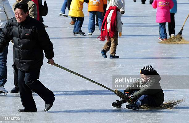 A child enjoys the ride seated on a broom and being pulled on the ice at a section of Shishahai Lake which remained open for the morning on February...
