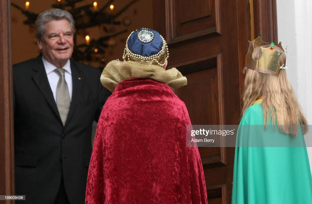 Child Epiphany carolers, known as Sternsinger in German, visit German President <a gi-track='captionPersonalityLinkClicked' href=/galleries/search?phrase=Joachim+Gauck&family=editorial&specificpeople=2077888 ng-click='$event.stopPropagation()'>Joachim Gauck</a> (L) at Bellevue presidential palace on January 6, 2013 in Berlin, Germany. The children walk from house to house in the days around January 6, singing carols and collecting money for needy children around the world, dressed as the Three Magi of the Christmas story in the Gospel of Matthew.
