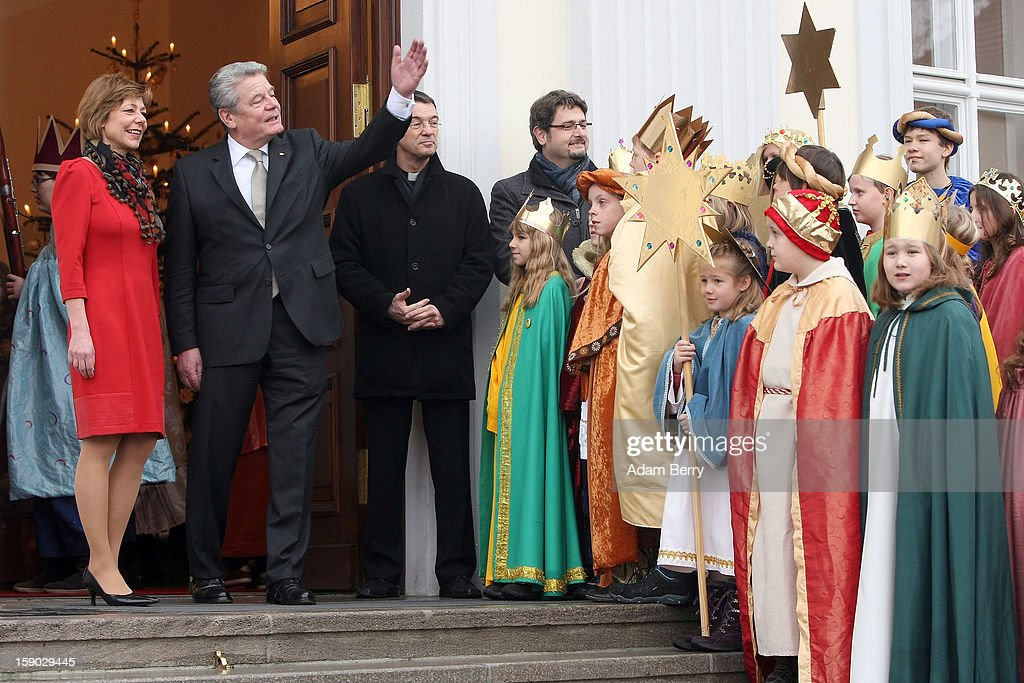 Child Epiphany carolers, known as Sternsinger in German, visit German President <a gi-track='captionPersonalityLinkClicked' href=/galleries/search?phrase=Joachim+Gauck&family=editorial&specificpeople=2077888 ng-click='$event.stopPropagation()'>Joachim Gauck</a> (2 from L) and his partner, <a gi-track='captionPersonalityLinkClicked' href=/galleries/search?phrase=Daniela+Schadt&family=editorial&specificpeople=7055235 ng-click='$event.stopPropagation()'>Daniela Schadt</a> (L), at Bellevue presidential palace on January 6, 2013 in Berlin, Germany. The children walk from house to house in the days around January 6, singing carols and collecting money for needy children around the world, dressed as the Three Magi of the Christmas story in the Gospel of Matthew.