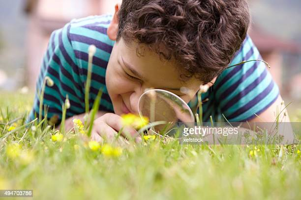 Child examining the nature with a magnifying glass