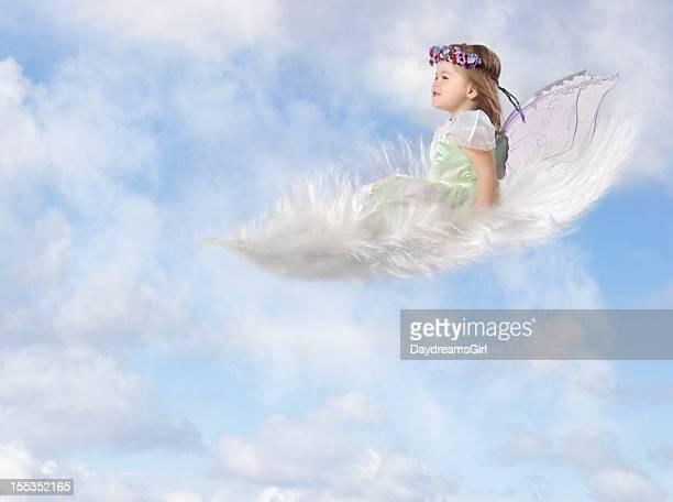 Enfant de fée sur blanc plumes flottant dans le ciel