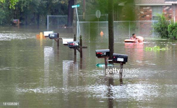 A child floats on a rubber dingy along flooded streets in Slidell northeast of New Orleans on August 30 2012 in Louisiana Tropical Storm Isaac has...