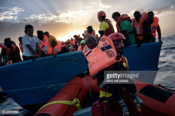 TOPSHOT A child from African origin is rescued from a distressed vessel by a member of Proactiva Open Arms NGO in the mediteranean sea some 20...