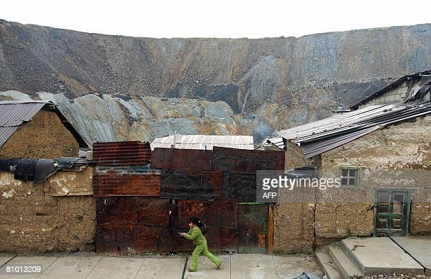 A child from the Champamarca neighborhood passes by a street and houses who are in the vicinty of piles of mineral waste from the Paragsha strip mine...