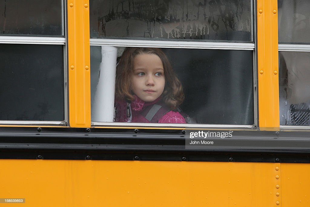 A child gazes from a school bus as it passes by the St Rose of Lima Catholic church while mourners gathered for a funeral service for shooting victim...