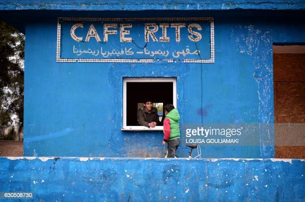 TOPSHOT A child gets a snack from a volunteer working in the kitchen of 'cafe Rits' in Ritsona refugee camp some 80 km north of Athens on December 21...