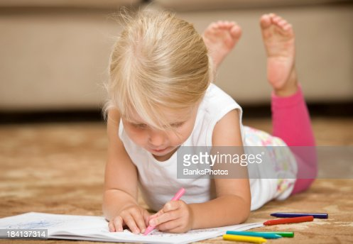 child girl coloring while lying down on living room rug stock photo getty images. Black Bedroom Furniture Sets. Home Design Ideas