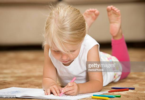 Child Girl Coloring while Lying Down on Living Room Rug