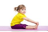 Child girl doing fitness exercises on gymnastic mat