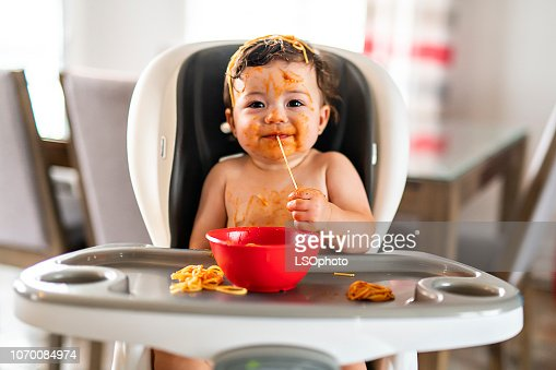 child girl, eating spaghetti for lunch and making a mess at home in kitchen : Stock Photo