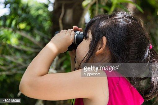 Child, Girl, mirando a través de binoculares : Foto de stock