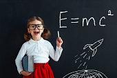 Child girl prodigy student with book near school blackboard