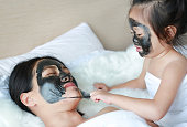 Child girl removed black mask from her mother, clean face.