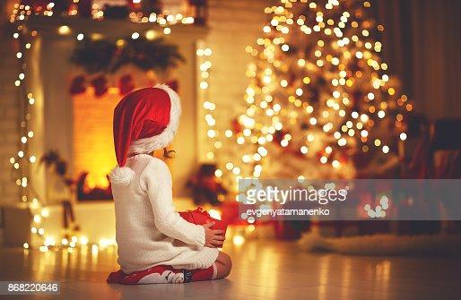 muchacha del niño sentarse frente a árbol de Navidad en la Nochebuena : Foto de stock