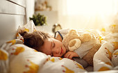child  girl sleeps in her bed with a toy teddy bear  in morning