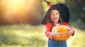 happy child girl with pumpkin outdoors in halloween