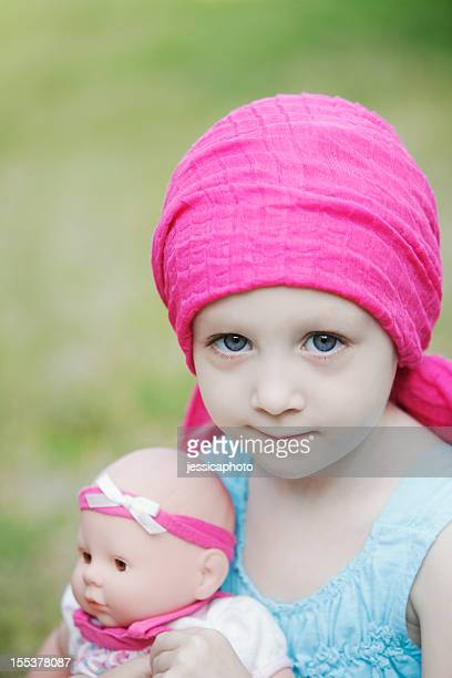 Child girl with scarf on her head holding a doll