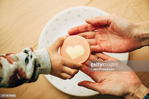 A child giving heart cookie to her mother
