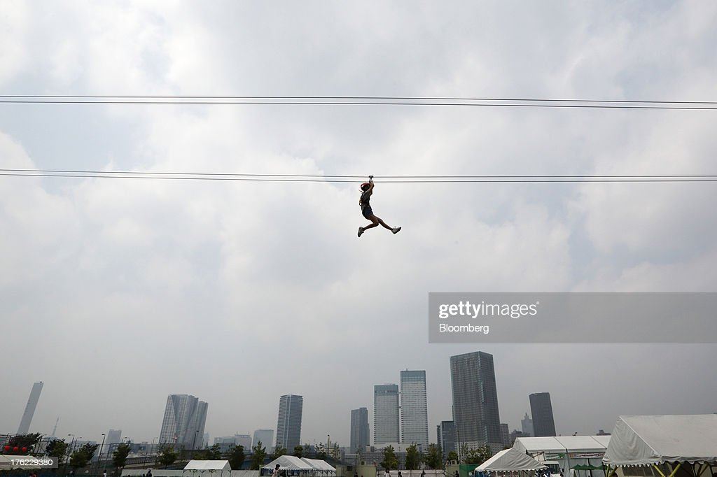 A child glides on a zip line past high rise buildings in Tokyo, Japan, on Monday, Aug. 12, 2013. Japan's economy slowed more than forecast in the second quarter as businesses cut investment, undermining gains in consumer and government spending that helped reduce deflationary pressures. Photographer: Tomohiro Ohsumi/Bloomberg via Getty Images