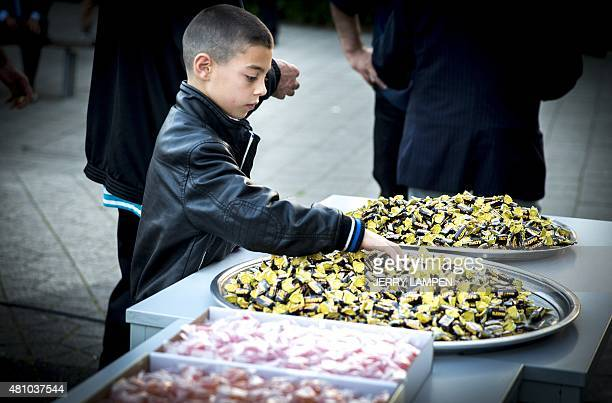 A child grabs sweets after the Eid alFitr prayers at the Mevlavana Mosque in Rotterdam on July 17 2015 Muslims around the world are celebrating Eid...