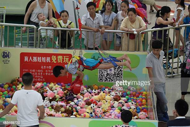 A child grabs toys acting as a claw after buckling up on a human claw machine at a shopping mall on August 7 2015 in Chongqing China