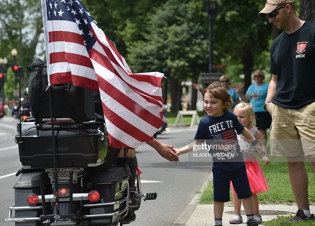 A child greets motorcyclists during the annual Rolling Thunder 'Ride for Freedom' parade ahead of Memorial Day in Washington, DC, on May 29, 2016. / AFP / MLADEN