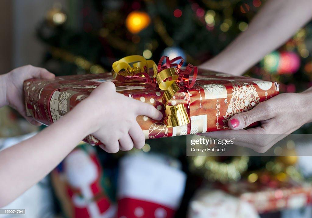 Child Handing Gift to Adult : Stock Photo