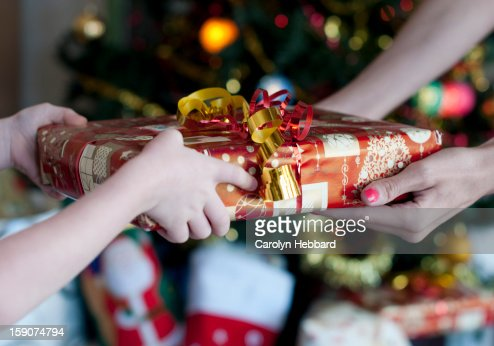 Child Handing Gift to Adult : Stock Photo