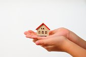 Young child indicating his love for his home in a conceptual image with his hands holding model of house on wite background. Adoption concep