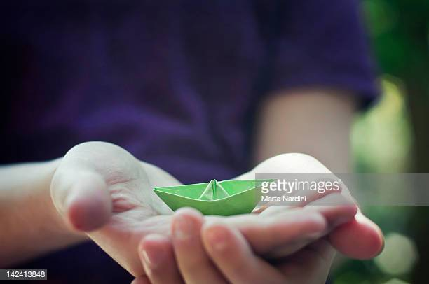 Child hands holding paper boat