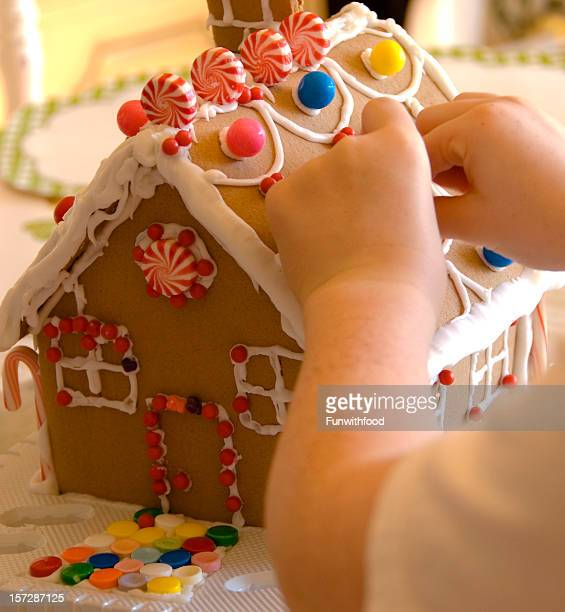 Child Hands Making Christmas Gingerbread Cookie House, Sweet Holiday Food