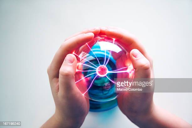Child hands touching plasma ball