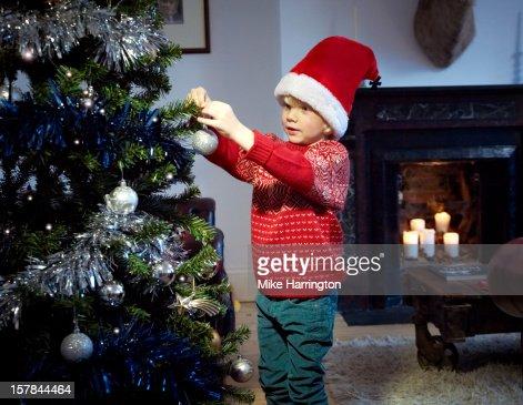 Child hanging bauble on Christmas tree. : Stock Photo
