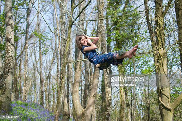 Child happy on a tree swing