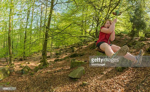 Child having fun on rope swing in summer forest