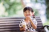 Child having ice-cream in park joyfully