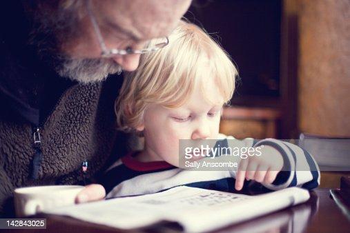 Child helping his Grandpa do crossword