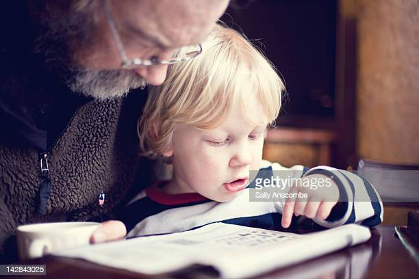 Child helping his Grandpa do crossword