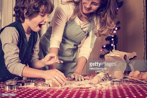 Child helping mother baking cookies for Christmas Eve