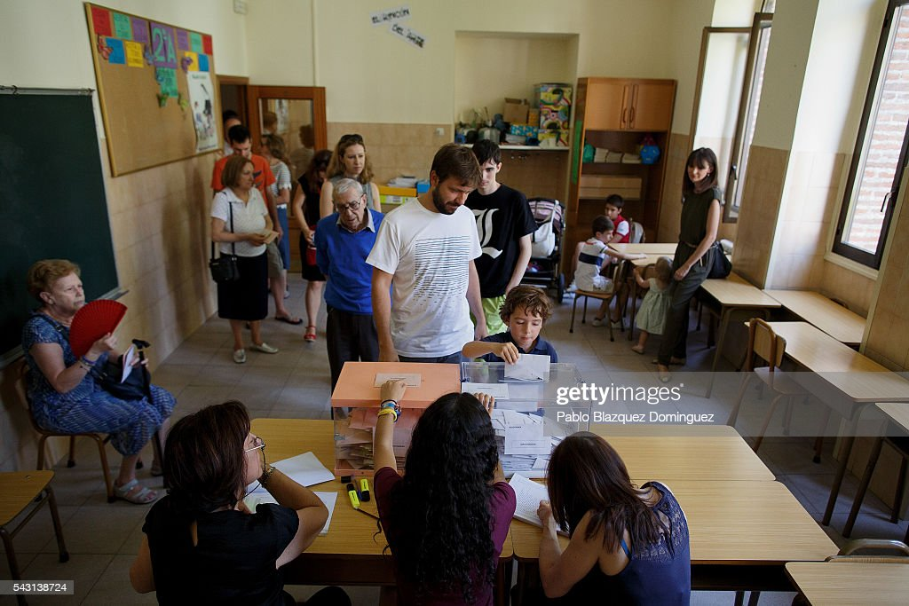 A child helps a man to cast his vote at a polling station during the Spanish General Elections on June 26, 2016 in Madrid, Spain. Spanish voters head back to the polls after the last election in December failed to produce a government. Latest opinion polls suggest the Unidos Podemos left-wing alliance could make enough gains to come in second behind the ruling center right Popular Party.
