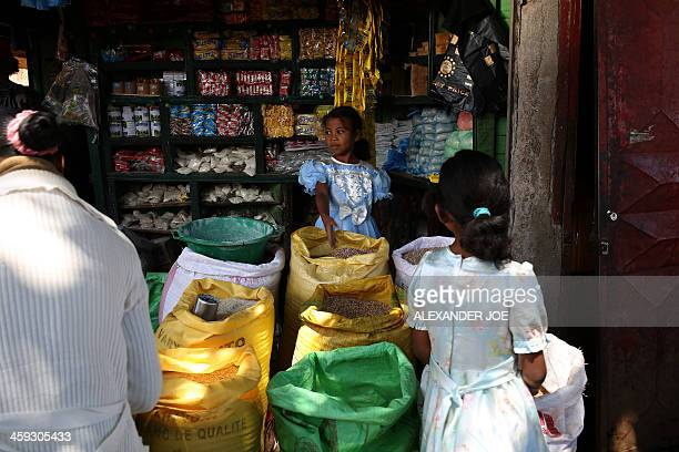 A child helps a parents shopping in Ambohibary 150 km south of Antananarivo on December 25 2013 Observers certified Madagascar's runoff presidential...