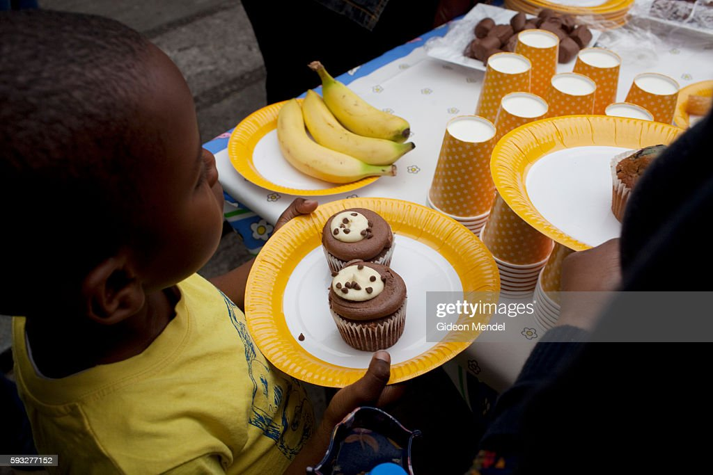 A child helps himself to some cake at a community tea party held in Clarence Road in Hackney exactly a week after the violent disturbances involving...